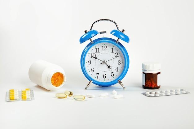 É hora de tomar seus comprimidos. um despertador em uma parede branca mostra a hora de tomar a medicação e, ao lado dela, - comprimidos médicos.