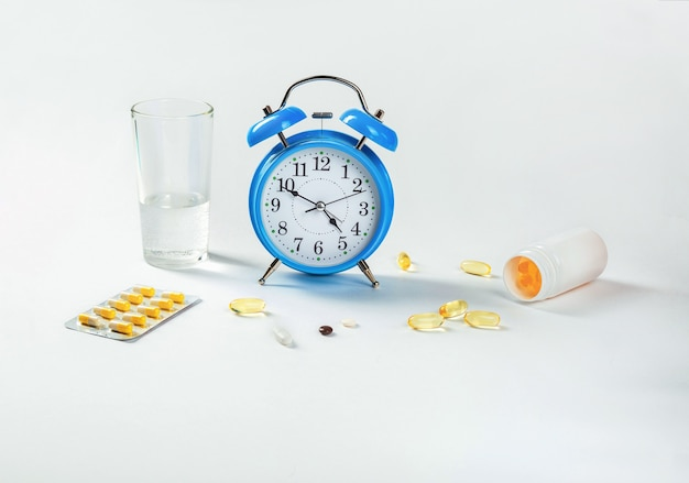 É hora de tomar seus comprimidos. um despertador mostra a hora de tomar a medicação e, ao lado dela, - comprimidos médicos.