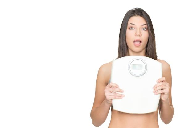 É hora de verificar seu peso. foto de estúdio de uma linda mulher segurando uma balança parecendo surpresa isolada em um branco copyspace ao lado