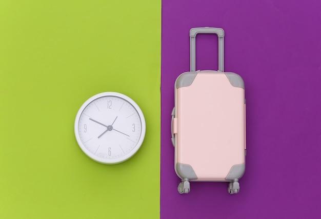 É hora de viajar. mini mala de viagem de plástico e relógio sobre fundo roxo verde. vista do topo. postura plana