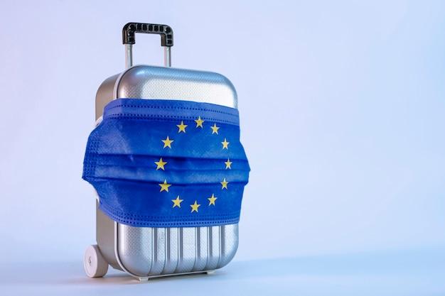 É hora de viajar. o conceito de descanso seguro durante uma pandemia de covid-19 coronavirus. mala de viagem com máscara médica e bandeira da união europeia.