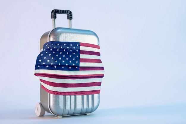 É hora de viajar. o conceito de descanso seguro durante uma pandemia de covid-19 coronavirus. mala de viagem com máscara médica e bandeira dos eua.