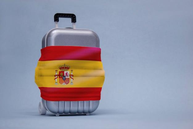 É hora de viajar. o conceito de descanso seguro durante uma pandemia de covid-19 coronavirus. mala de viagem com máscara médica e bandeira espanhola.