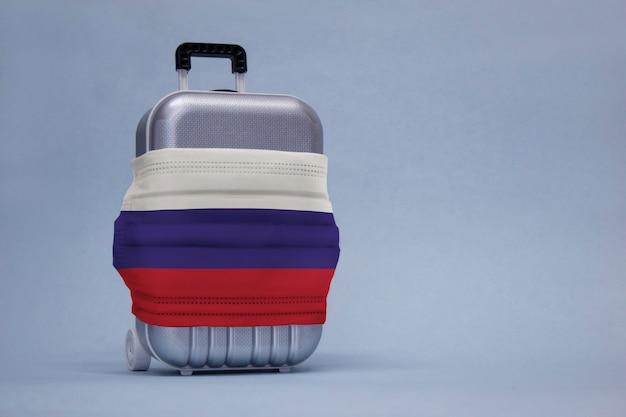 É hora de viajar. o conceito de descanso seguro durante uma pandemia de covid-19 coronavirus. mala de viagem com máscara médica e bandeira russa.