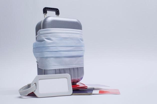 É hora de viajar. o conceito de descanso seguro durante uma pandemia de covid-19 coronavirus. mala de viagem com máscara médica
