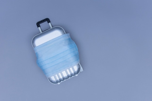 É hora de viajar. o conceito de descanso seguro durante uma pandemia de covid-19 coronavirus. mala de viagem com máscara médica.