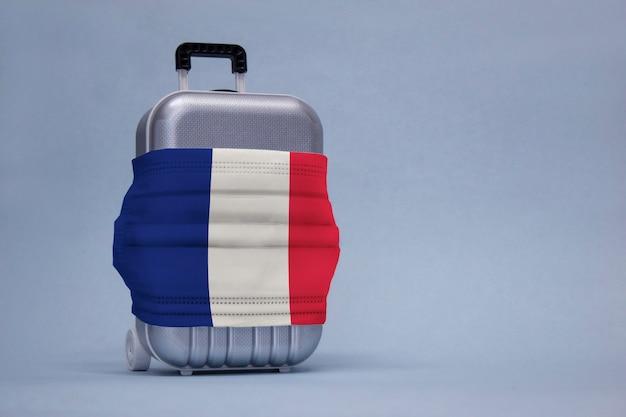 É hora de viajar. o conceito de descanso seguro durante uma pandemia de covid-19 coronavirus. mala para viajar com uma máscara médica e a bandeira da frança.