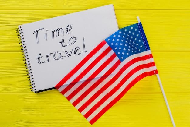 É hora de viajar para os eua. bandeira dos eua e o bloco de notas na mesa de madeira amarela no fundo.