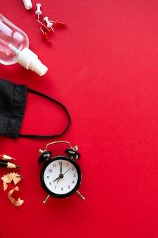 É hora de voltar às aulas em uma nova realidade, escolaridade leiga após a pandemia de coronavírus, material escolar, máscara protetora e anti-séptico em um fundo vermelho