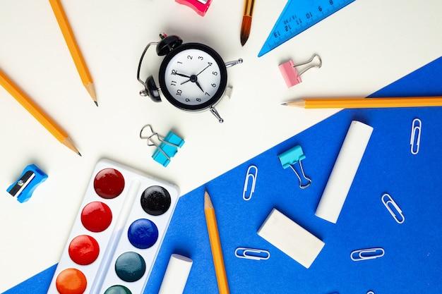É hora de voltar para a escola. vista superior de artigos de papelaria e despertador