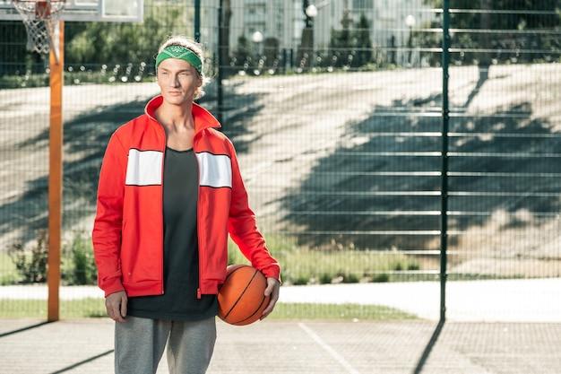 É hora do esporte. homem simpático e simpático em pé no campo de esportes enquanto vem para jogar basquete