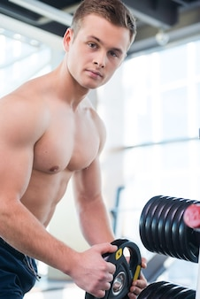 É importante escolher o peso certo. homem jovem e musculoso confiante escolhendo o peso para levantar enquanto está de pé na academia