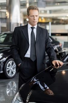 É isso que eu quero. homem de negócios de cabelos grisalhos escolhendo um carro novo
