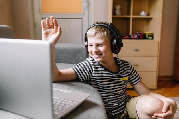 E-learning da videoconferência do aluno do menino com o professor no laptop na sala de estar em casa. ensino doméstico e ensino à distância, online, educação e internet.