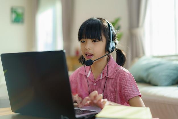E-learning de videoconferência de aluna asiática com professor e colegas no computador na sala de estar em casa.