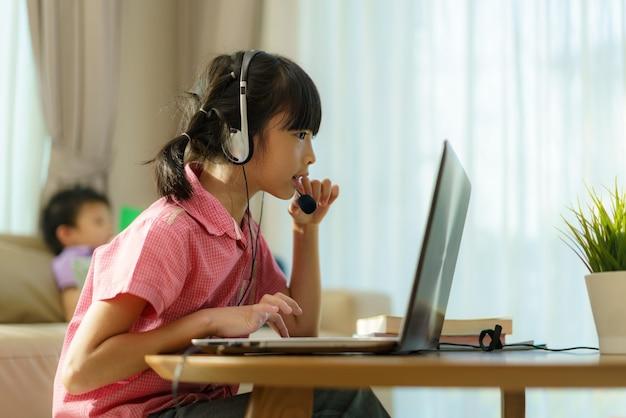 E-learning por videoconferência de aluna asiática com professora e colegas de classe no computador e seu irmão lendo um livro no sofá da sala de casa