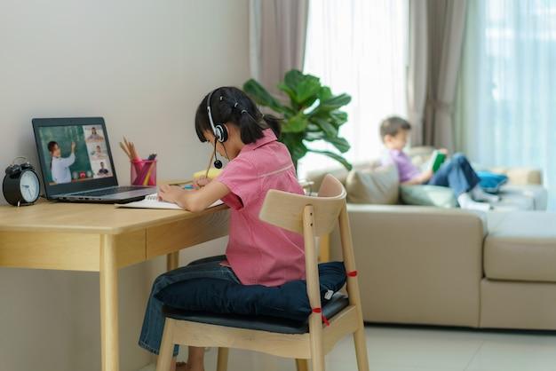 E-learning por videoconferência de aluna asiática com professora e colegas de classe no computador e sua irmã lendo um livro na sala de estar de casa