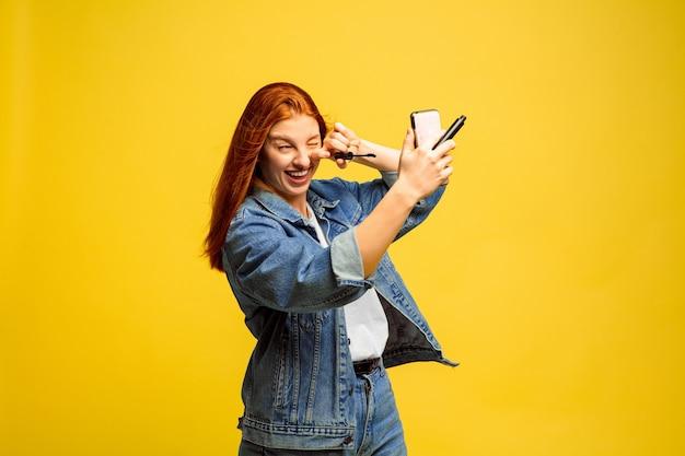 É mais fácil ser seguidor. não precisa de selfie para maquiagem. retrato de uma mulher caucasiana em fundo amarelo. modelo de cabelo vermelho feminino lindo. conceito de emoções humanas, expressão facial, vendas, anúncio.