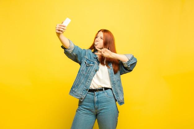 É mais fácil ser seguidor. precisa de roupas mínimas para selfie. retrato de uma mulher caucasiana em fundo amarelo. modelo de cabelo vermelho feminino lindo. conceito de emoções humanas, expressão facial, vendas, anúncio.