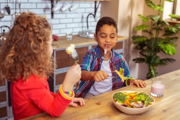 É meu. crianças satisfeitas olhando para a tigela enquanto saboreiam uma salada fresca