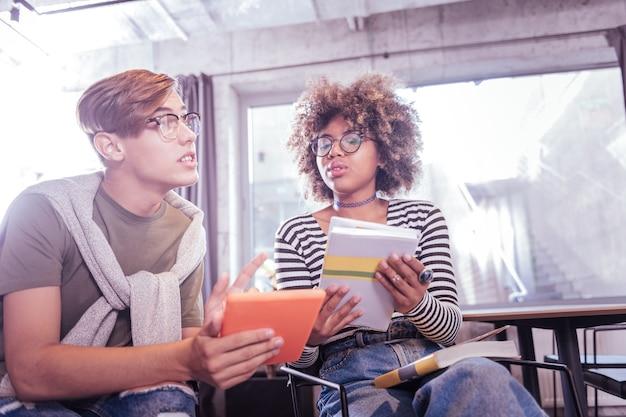 É meu. mulher atenta olhando para o livro enquanto fala com o parceiro