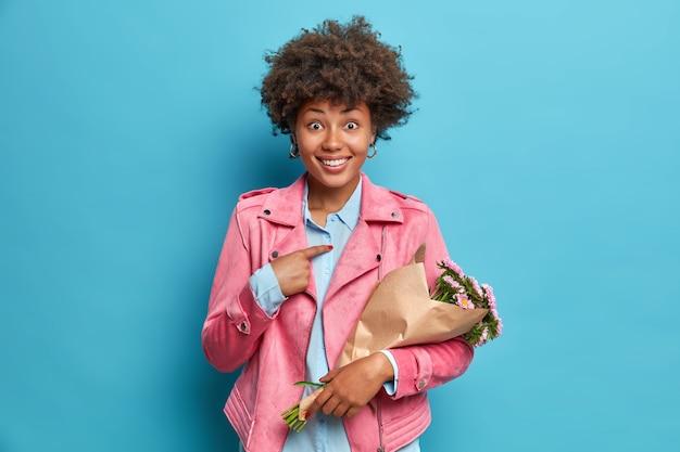 É para mim. jovem alegre aponta para si mesma feliz por receber um buquê de flores e usa uma jaqueta rosa isolada sobre uma parede azul