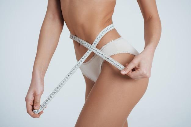 É por isso que você deve começar a fazer exercícios. menina na cueca branca com fita métrica em volta da cintura.