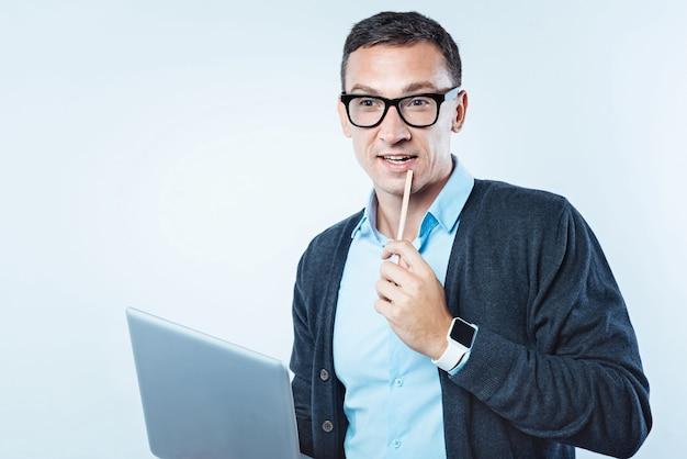 E se. cara pensativo de óculos, tocando seu queixo com um lápis enquanto olha para a vaga e sonha durante o trabalho em um projeto de negócios.