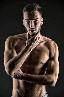 E se eu te mostrar meus músculos. o rosto pensativo do homem parece atraente fundo preto. atleta corpo musculoso sexy no rosto confiante. homem muscular torso tenso, veias, músculos, tocam o queixo enquanto pensa.
