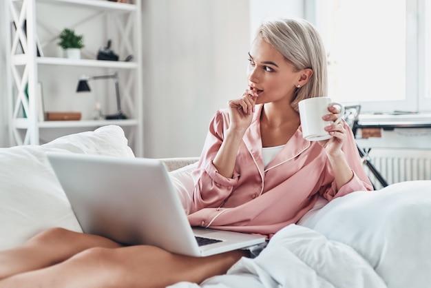 E se ... mulher jovem e atraente olhando para longe e usando o laptop enquanto está sentada na cama em casa