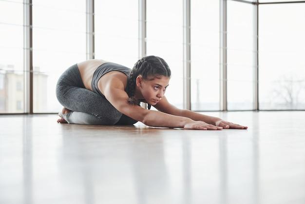 É sempre necessário estar pronto. aqueça no chão de madeira. garota jovem fitness está se preparando para uma sessão