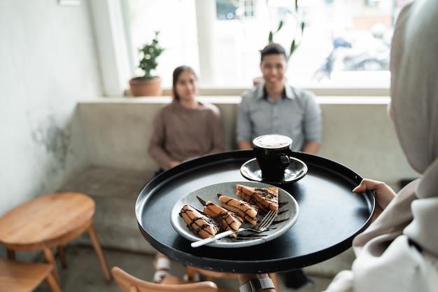 É servido um copo de café e torradas em uma bandeja