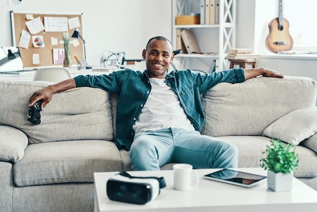 É tão bom estar em casa! africano jovem bonito olhando para a câmera e sorrindo enquanto está sentado dentro de casa