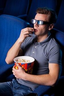 É tão realista! vista superior de um jovem animado em óculos tridimensionais comendo pipoca e assistindo filme enquanto está sentado no cinema