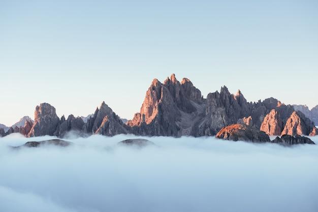 É tudo maior do que você pensa. os picos das montanhas sufocam por causa de uma névoa densa. foto inacreditável tira.