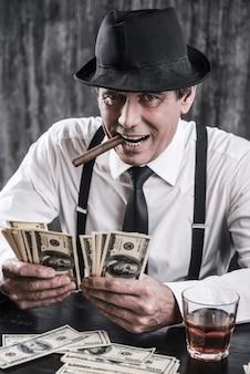É tudo meu! gangster sênior de camisa e suspensórios contando dinheiro e olhando para você com um sorriso enquanto está sentado à mesa