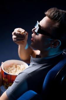 É um filme tão realista! vista superior de um jovem animado em óculos tridimensionais comendo pipoca e assistindo filme enquanto está sentado no cinema