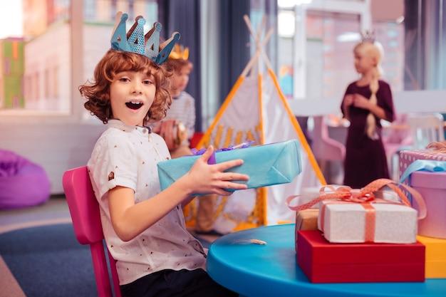 É um segredo. menino alegre sentado em primeiro plano segurando uma caixa de presente