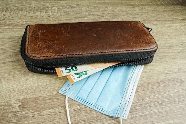 É uma carteira de couro marrom com notas de euro sobre a mesa e as notas são visíveis dentro da carteira