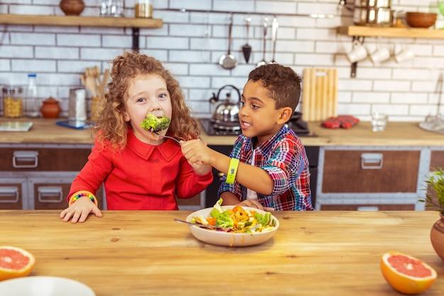 É uma delícia. garota incrível comendo brócolis enquanto olha para a câmera