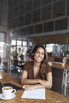 E uma mulher hispânica de sucesso sorrindo trabalhando em um café