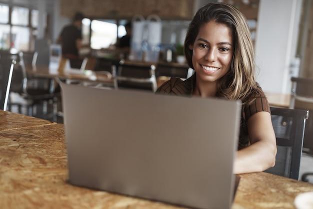E uma mulher hispânica de sucesso sorrindo usando laptop no café