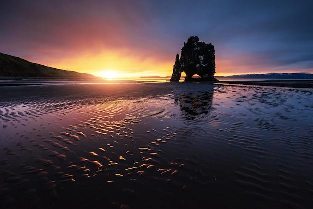 É uma rocha espetacular no mar na costa norte da islândia. as lendas dizem que é um troll petrificado. neste hvitserkur reflete na água do mar após o pôr do sol da meia-noite