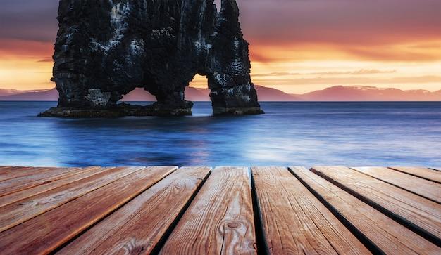É uma rocha espetacular no mar na costa norte da islândia