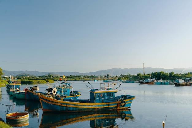 E velhos barcos azuis no lago durante o dia