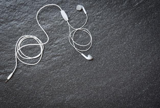 Earphons na visão de topo escura / música é a minha vida e entretenimento ouvir o conceito de música