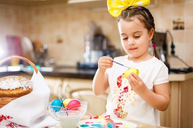 Easter feliz uma menina da criança bonita que pinta ovos da páscoa.