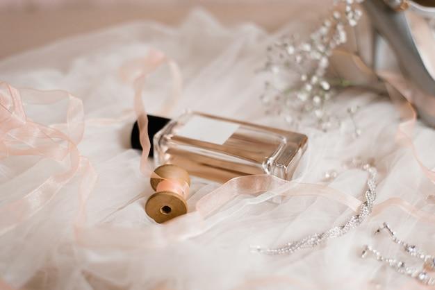 Eau de toilette, bijuterias e um raminho de gypsophila em um tule branco. manhã da noiva