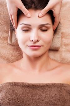 Eautiful jovem relaxado mulher desfrute recebendo massagem de rosto no salão de spa