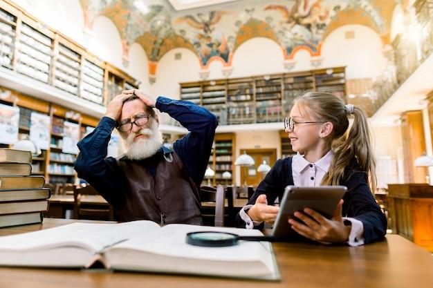 Ebook, livro, tecnologia, computador versus conceito tradicional de livros impressos. menina bonita detém ebook ou tablet e mostra para seu avô surpreso e animado